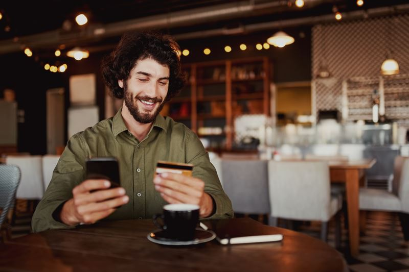 Man using phone in coffee shop